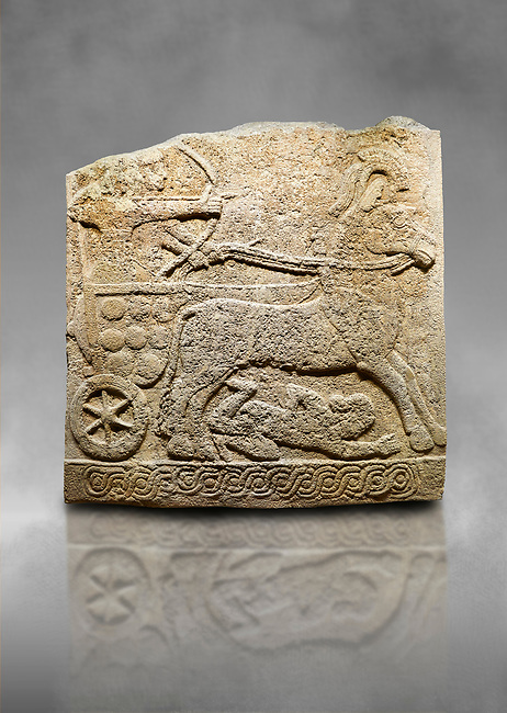 Hittite relief sculpted orthostat stone panel of Long Wall Limestone, Karkamıs, (Kargamıs), Carchemish (Karkemish), 900 -700 B.C. Anatolian Civilisations Museum, Ankara, Turkey<br /> <br /> Chariot. One of the two figures in the chariot holds the horse's headstall while the other throws arrows. There is a naked enemy with an arrow in his hip lying face down under the horse's feet. It is thought that this figure is depicted smaller than the other figures since it is an enemy soldier. The lower part of the orthostat is decorated with braiding motifs.<br /> <br /> On a grey art background.