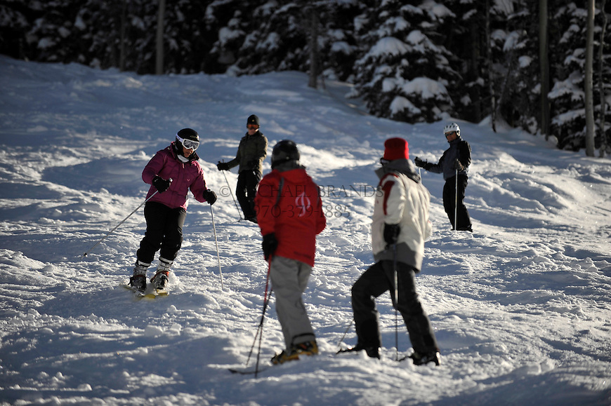 Shireen Day, far left, 47, of Boulder, CO, tackles some intermediate bumps on Aspen Mountain under the watchful eye of her instructor and fellow students. Michael Brands for The New York Times.