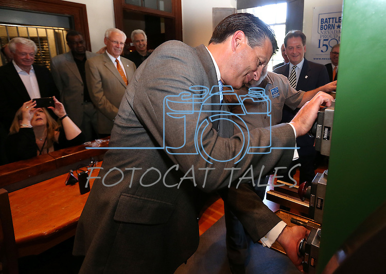 Gov. Brian Sandoval mints the first medallion at a ceremony marking the beginning of production of the fourth and final medallion in a commemorative Sesquicentennial series at the Nevada State Museum, in Carson City, Nev., on Wednesday, Sept. 3, 2014. <br /> Photo by Cathleen Allison