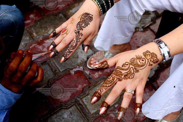 Girls hands are painted with mehendi patterns.