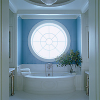 The custom-built five-foot oculus window echoes the curves of the bath in the master bathroom of this New York apartment