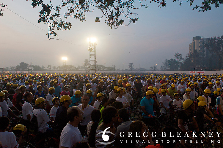 A sea of 7,500 participants illuminated under a single spotlight wait at dawn in the holding area at the start of the 2010 Mumbai Cyclothon citizen festival ride.  Reebok  provided the yellow helmet freebies for all participants. - Bombay/Mumbai - India
