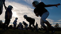 Youth league football players are silhouetted against the sky as the sun sets on practice