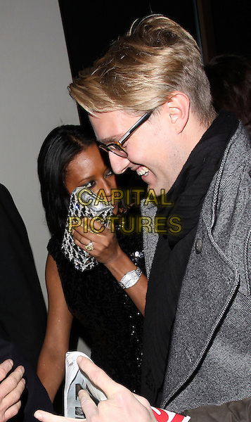 MEL B - MELANIE BROWN - SCARY SPICE & FAN.Leaving the launch of the OMEGA Constellation 2009 collection, Berkely Street, London, England..October 15th, 2009.half length black dress sequins sequined silver clutch bag glasses profile watch whispering talking .CAP/AH.©Adam Houghton/Capital Pictures.