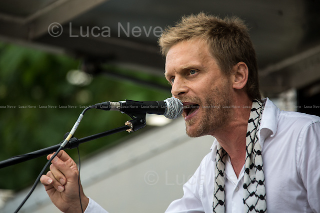 Dave Randall (Faithless and Slovo guitarist, producer and composer).<br /> <br /> London, 26/07/2014. A week after the c.100,000 people who marched from 10 Downing Street to the Israeli Embassy, today another national demonstration saw tens of thousands of people taking to the street of central London in support and solidarity with Gaza's population, battered by an 18-day long campaign of Israeli sea/air bombardments and by the terrestrial invasion. The number of Palestinians killed during the Israeli raids overtook 1000 people including a large number of children, and thousands of injured people. After gathering outside the Israeli embassy in High Street Kensington, the sea of people marched through central London, ending in Parliament Square. The march was organised by, amongst others, War On Want, Stop The War Coalition, London Palestine Action, FOA - Friends of Al Aqsa, PSC - Palestine Solidarity Campaign, BMI - British Muslim Initiative, Palestinian Forum in Britain, and Campaign for Nuclear Disarmament.