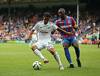 Pictured L-R: Kyle Naughton of Swansea is challenged by Yannick Bolasie of Crystal Palace<br />