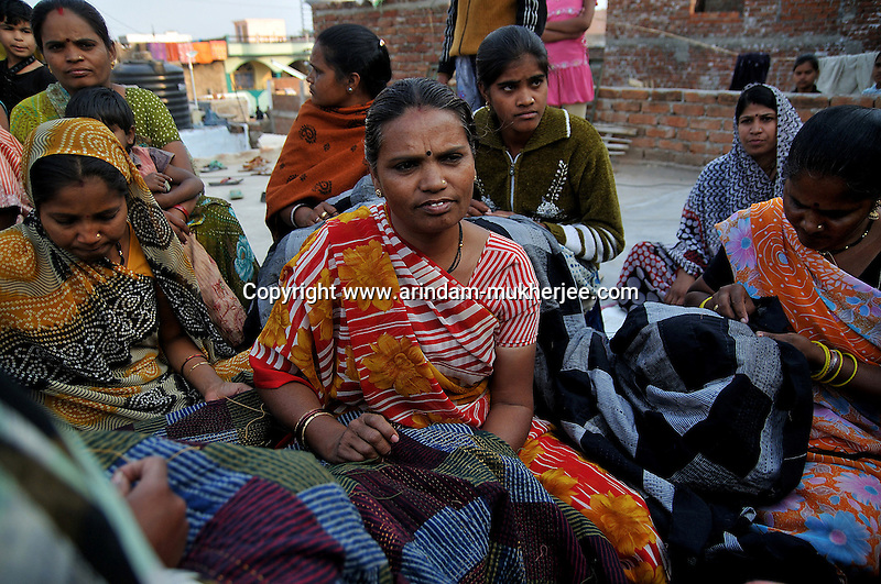 Sheela Devi (center) and other workers of 'Sadhna' working on their assignments. After finishing their household daily chore they do the assignments in leisure. Ratakhet slum in Udaipur, Rajasthan, India. 24.1.2011. Arindam Mukherjee