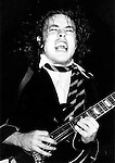 AC/DC's Angus Young plays guitar onstage at the Palladium in August 1978.