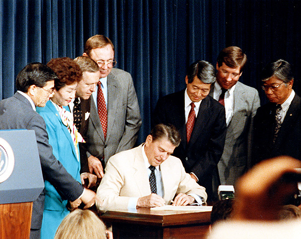 """President Reagan signs HR 442 into law in White House ceremony. From left to right: Rep. Norman Y. Mineta (D-CA), Rep. Pat Saiki (R-HI), Sen. Pete Wilson (R-CA), Rep. Don Young (R-AK), Rep. Robert T. Matsui (D-CA), Rep. Bill Lowery (R-CA) and Harry Kajihara, President of the Japanese American Citizens League."""