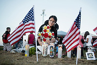 Heloise Morenl (cq), 12, places flowers at a shrine during a vigil held next to the Aurora Century 16 movie theater where James Holmes (cq), 24, is in custody and is suspected of killing 12 people and wounding many more in Aurora, Colorado, Friday, July 20, 2012. The shootings occurred during the midnight premiere of the new Dark Knight Batman movie...Photo by MATT NAGER