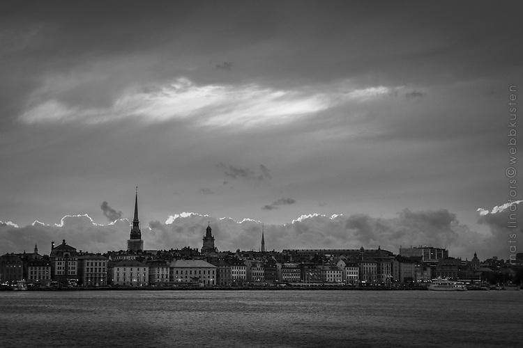 Kvällsmoln över Skeppsbron i Gamla stan Stockholm i svartvitt.