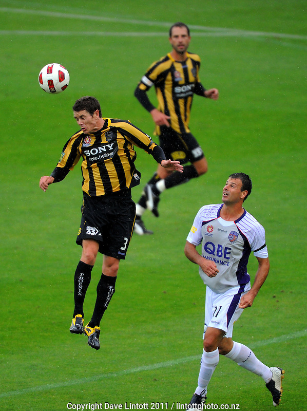 Phoenix' Tony Lochhead wins a header under pressure from Mile Sterjovski. A-League football - Wellington Phoenix v Perth Glory at Westpac Stadium, Wellington, New Zealand on Sunday, 23 January 2011. Photo: Dave Lintott / lintottphoto.co.nz