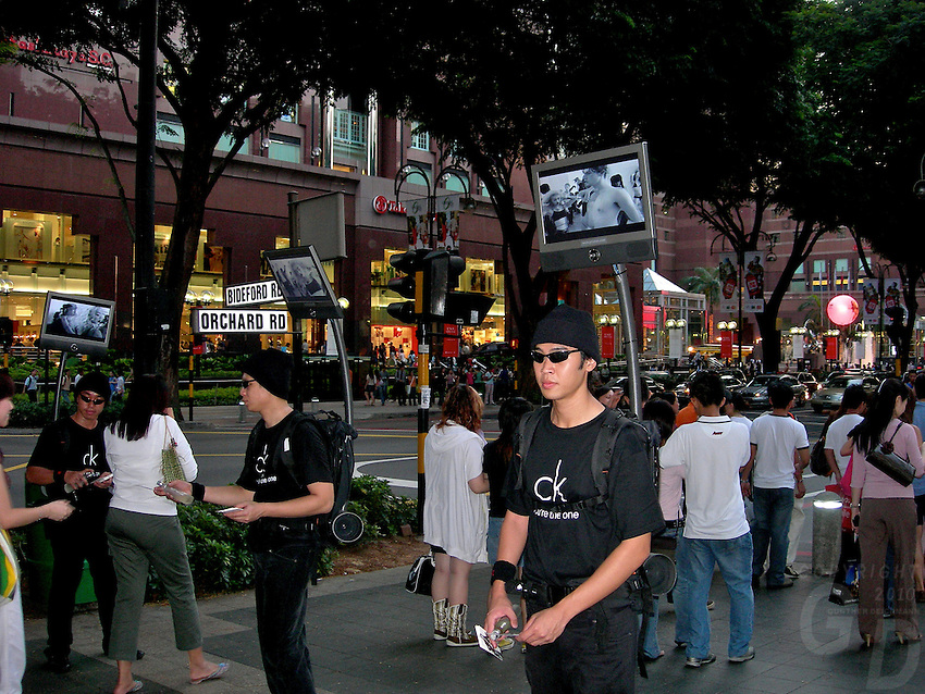 An electronic sales man in the street of Singapore, high tech advertising, Singapore