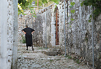 Woman walking in a narrow cobbled street in the old town of the hilltop town of Himare, in Vlore in the Albanian Riviera on the Ionian Coast, Southern Albania. Picture by Manuel Cohen