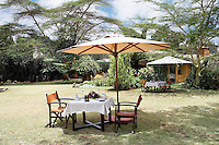 The grounds of a luxury guest house where red cedar tables laid for dinner and shaded by parasols are dotted around the garden.