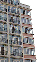 Migrant workers clean windows outside a high-rise residential building without wearing safety belt, Beijing, China.  The concept of establishing and maintaining a safety conscious work environment is still very low in China and the number of window cleaners fall from height in the workplace has been increasing since they didn't use proper tools and proper protection during the work. .30 Aug 2010