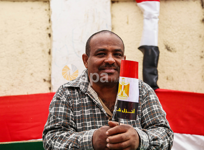 An Egyptian man holds the Egyptian flag on the first day of the 2018 Egyptian presidential elections, outside a polling station, in Cairo, Egypt, on March 26, 2018. Egyptians head to the polls in a three-day vote to choose between incumbent Abdel Fattah al-Sisi and candidate Moussa Mostafa Moussa. Photo by Fayed El-Geziry
