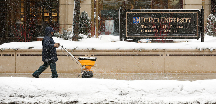 David Febo (cq) lays down a layer of salt to keep the sidewalks clear on the Loop campus of DePaul University in Chicago Thursday, Jan. 2, 2014. The New Year brought two days of lake effect snows to the downtown campus.  (Photo by Jamie Moncrief)