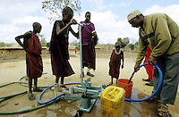 TANZANIA, Handeni, Massai children pump water from rain water cistern / TANSANIA, Handeni, Massai Kinder pumpen Trinkwasser mit einer Pumpe aus einem Regenwasserspeicher, Zisterne