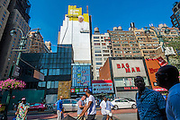 New York, NY 29 August 2015 - A mural of Pope Francis emerges in Midtown as the City prepares for the Papal Visit in September. The signage space is about 225 feet high and 93 feet across, according to Lamar Outdoor Advertising, which has leased the wall and sold ad space on it for many years. Painters expect to use about 100 gallons of paint for the mural which will remain in place for six weeks