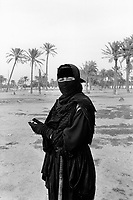 Iraq. Basra. A young woman wears the niqab (a cloth which covers the face) and the abaya (body-covering black garments). She is a sheppherd who looks after her herd in a deserted amusement park built in the seventies. The abaya, sometimes also called aba, is a simple, loose over-garment, essentially a robe-like dress, worn by some women in parts of the Islamic world. Traditional abaya are black and may be either a large square of fabric draped from the shoulders or head or a long caftan. The abaya covers the whole body except the face, feet, and hands. It can be worn with the niqab, a face veil covering all but the eyes. Some women choose to wear long black gloves, so their hands are covered as well. Basra ( in arabic Al Basrah) is the capital of Basra Governorate in southern Iraq. 01.03.04 © 2004 Didier Ruef