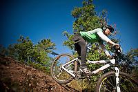 A female rider descends a rock outcrop while mountain biking in Copper Harbor Michigan Michigan's Upper Peninsula.