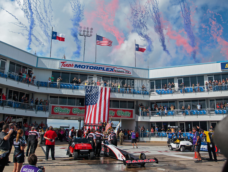 Oct 7, 2018; Ennis, TX, USA; Pyrotechnics explode at the conclusion of the national anthem behind the car of NHRA top fuel driver Billy Torrence during the Fall Nationals at the Texas Motorplex. Mandatory Credit: Mark J. Rebilas-USA TODAY Sports
