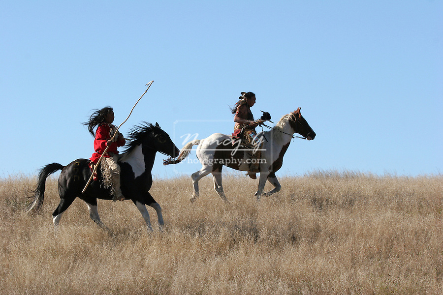 Two Native American Indians riding horseback looking for ememies through the prairie of South Dakota