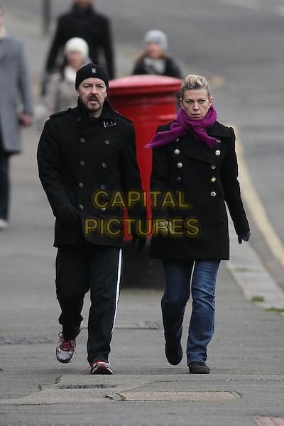 Ricky Gervais, Jane Fallon.walking in Primrose Hill, London, England 29th December 2011.full length couple jeans denim black coat jacket beanie hat purple pink scarf facial hair gloves .CAP/HIL.©John Hillcoat/Capital Pictures .