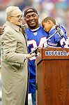 9 October 2005: Ralph C. Wilson (left), owner of the Buffalo Bills introduces Thurman Thomas (holding his son) at Ralph Wilson Stadium, in Orchard Park, NY. Thurman Thomas, former running back for the Buffalo Bills and 2006 Hall of Fame Candidate, is honored during halftime in a game between the Buffalo Bills and the Miami Dolphins. The Bills defeated the visiting division rival Dolphins 20-14. ..Mandatory Photo Credit: Ed Wolfstein