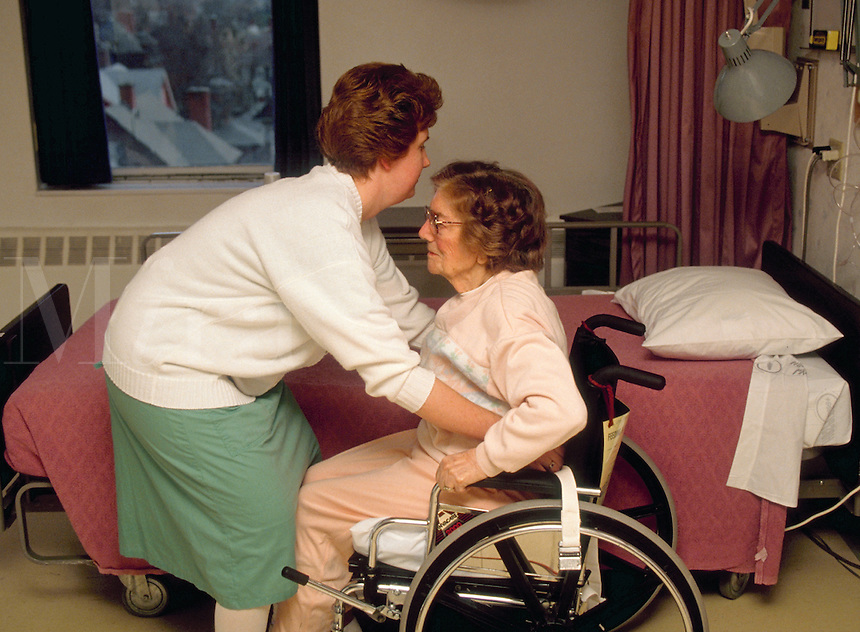 A senior woman is assisted into a wheelchair at a nursing home.