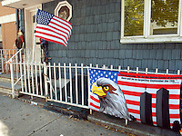 "USA. New York City. Brooklyn. Outside a private house on the railing, a banderole with a drawing of a bald eagle, an american flag and the Twin Towers ( World Trade Center ). The words say: ""Time is passing. Yet, for the United States of Amercia, there will be no forgetting. September the 11th 2001. Georges W. Bush"".  American flag blowing in the wind. Near the door's entrance, an Halloween house decoration. 20.10.2011 © 2011 Didier Ruef"