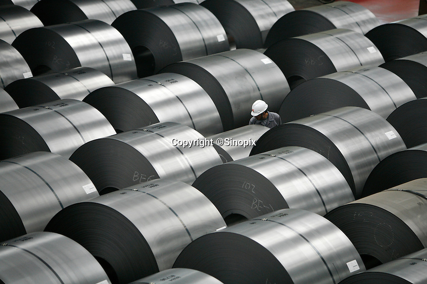 A worker inspects and marks rolls of steel plates at Ma Steel (Maanshan Iron & Steel Co.) in Maanshan, Anhui Province, China..