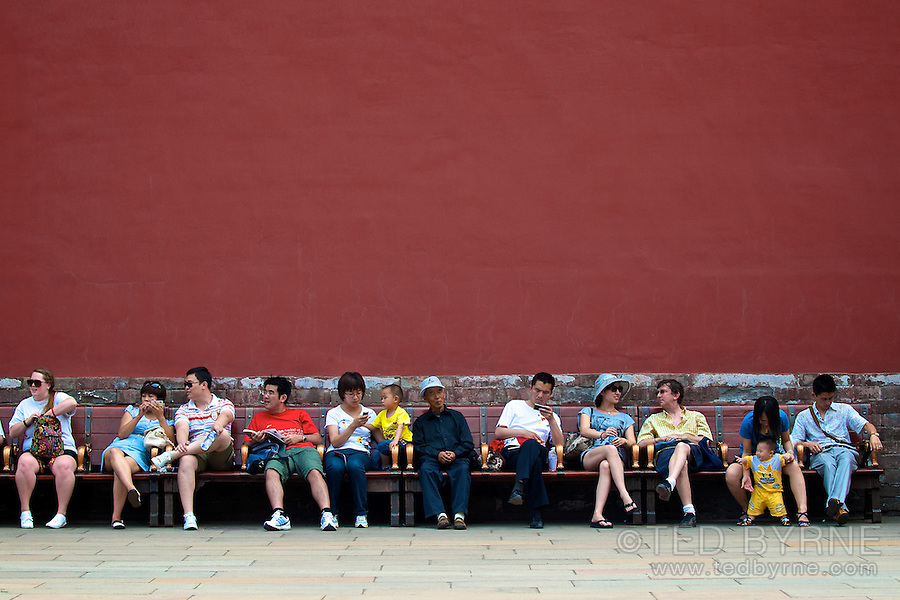 A group of mostly Chinese people sitting relaxing after visiting the Forbidden City in Beijing