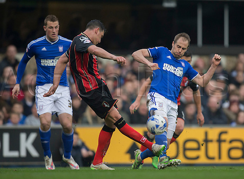 03.04.2015.  Ipswich, England. Skybet Championship. Ipswich Town versus AFC Bournemouth. Ipswich Town's Luke Varney (right) looks to block the clearance from Bournemouth's Tommy Elphick.