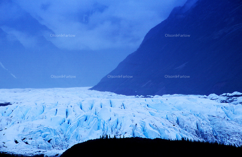 The Matanuska Glacier, a large 24 mile long and 4 mile wide ice flow.  It is aan active glacier advancing one foot a day on a valley floor.  Most Alaskan glaciers are smaller alpine glaciers hanging off mountain slopes.  ....It is blue because the density of glacier ice allows the entire spectrum of light to be absorbed with the exception of the blue light which is reflected, and can therefore be seen by your eye.