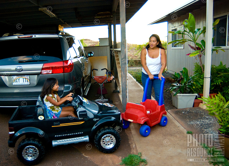 Mom and young daughter in driveway of home with toys and cars