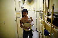 "Kam Chung, 49, adjusts his medical corset between wooden boxes people use for living early October 9, 2012 in Hong Kong. In Hong Kong's middle-class residential area, short distance from its shopping and financial districts, 24 people live in ""coffin homes"" packed in a single apartment of little over 50 square meters. Its residents pay monthly 1450 Hong Kong dollars (around 180 USD) for their living space built of wooden panels of 2 meters by 70 cm. To maximize income from the rent in central Hong Kong, landlords build such coffin homes, nicknamed because of their resemblance to real coffins. Space has always been at a premium in Hong Kong where developers plant high-rises on every available inch.   REUTERS/Damir Sagolj (CHINA)"