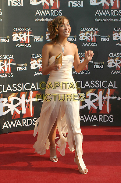 MYLEENE KLASS.Attends the Classical Brit Awards 2004 at The Royal Albert Hall, London..full  length full-length strapless floaty dress side split showing leg clutch bag laughing smiling.www.capitalpictures.com.sales@capitalpictures.com.©Capital Pictures