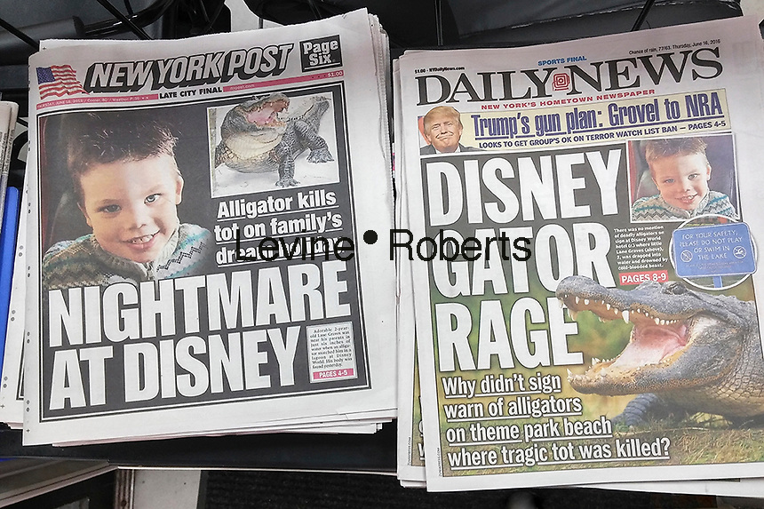The headlines of the New York Daily News and Post on Thursday, June 16, 2016 report on the death of 2 year old Lane Graves who was dragged and drowned by an alligator in Orlando, Florida. The attack occurred in a lake on Disney World property. (© Richard B. Levine)