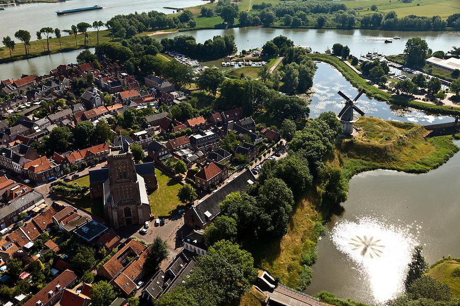 Nederland, Noord-Brabant, Woudrichem, 08-07-2010; vestingstad in Land van Heusden en Altena. Gelegen op de plaats waar de Maas (nu Afgedamde Maas) in de Waal stroomt en verder gaat als Boven-Merwede. In het centrum de  Martinuskerk, buiten de stadsmuren molen Nooit Gedagt (korenmolen)..Fortified town in Land of Altena. Located at the place where the Maas (Meuse) flows in the river Waal river, continuing under the name of Boven-Merwede. In the center church of Saint Martin, outside the city walls the mill Never thought fit (flour mill)..luchtfoto (toeslag), aerial photo (additional fee required).foto/photo Siebe Swart.