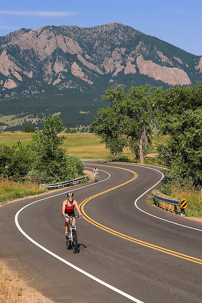 Woman cycling on county road with Flatirons rock formation behind, Boulder, Colorado, USA. .  John leads private photo tours in Boulder and throughout Colorado. Year-round. .  John offers private photo tours in Denver, Boulder and throughout Colorado. Year-round.