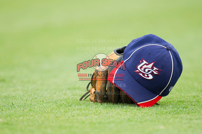 A Team USA hat rests on top of a glove in the outfield during the USA Baseball 18U National Team Trials at the USA Baseball National Training Center on June 30, 2010, in Cary, North Carolina.  Photo by Brian Westerholt / Four Seam Images