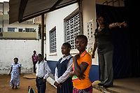 """MONROVIA, LIBERIA - FEBRUARY 17: Vice principal, Venoria Crayton, addresses students at morning assembly on the second day of school, since schools closed due to the Ebola outbreak 6 months ago, at the C.D.B. King Elementary School on February 17, 2015 in Monrovia, Liberia. Ebola destroyed and devastated our land,'' Venoria Crayton, the vice principal, told her pupils. """"It brought us sadness, it brought us pain. Some of your neighbors died, right? Some of your neighbor's children died, right? But you are here."""" Though Ebola cases have receded into the single digits in Liberia, lingering fear and a depressed economy have dampened the turnout at schools. Many have yet to reopen, having failed to meet the minimum requirements put in place to prevent the transmission of the virus. Many of those that have reopened – like C.D.B. King, which, though located in the center of the capital, lacks electricity and running water, and has only a few toilet stalls for a student population that numbered 1,000 before Ebola — are struggling.<br /> Daniel Berehulak for The New York Times"""