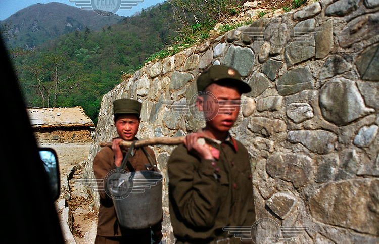 Young soldiers carrying a pail perform road repair works on a mountain road..