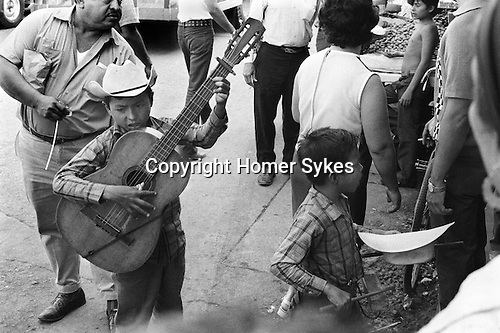 Mazatlan Mexico. Children busking in the street, brother, young sibling collecting in his hat and playing a simple wooden percussion block.