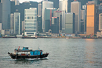 Sampan heading across Victoria Harbour in the morning, with the Kowloon skyline in the background, Hong Kong Island, Hong Kong, China.