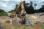 A good excavator operator uses the arm and excavator like an extension of his body.  In this photo, he is just reaching out ot move the trench box.