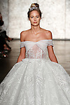 Model walks runway in an off the shoulder feather embroidered grand finale ballgown, from Inbal Dror Fall 2018 bridal collection on October 5, 2017; during New York Bridal Fashion Week.