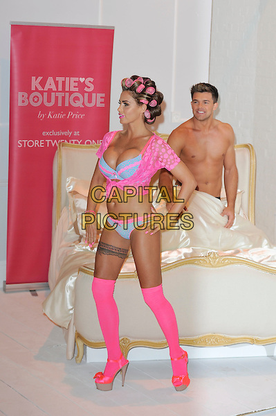 Katie Price (Jordan) & Leandro Penna.The launch photocall for Katie Price's new summer lingerie range for Store 21, The Worx, London, England..May 29th, 2012.full length pink lace top knotted bra cleavage belly stomach midriff knickers underwear tights stockings tattoo garter beige platform sandals shoes rollers curlers in hair side bed chest topless couple hand on hips side profile funny.CAP/MAR.© Martin Harris/Capital Pictures.